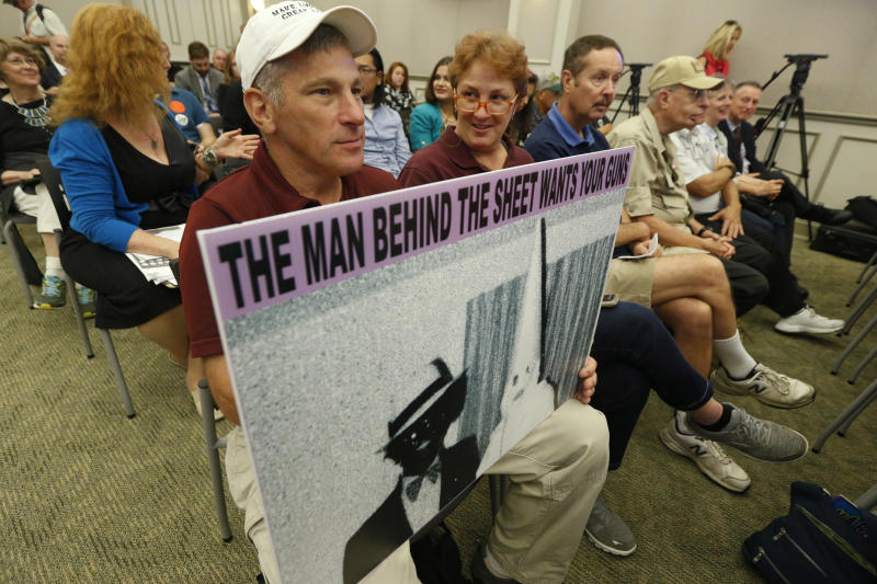 Ed Gomez, of Fairfax, Va., holds a sign depicting a photo that was on Gov. Northam's facebook page as he attends the second day of a Virginia Crime Commission meeting on gun issues at the Capitol in Richmond, Va., Tuesday, Aug. 20, 2019. Democratic Gov. Ralph Northam called the special session after a city employee opened fire in a Virginia Beach municipal complex May 31. (AP Photo/Steve Helber)
