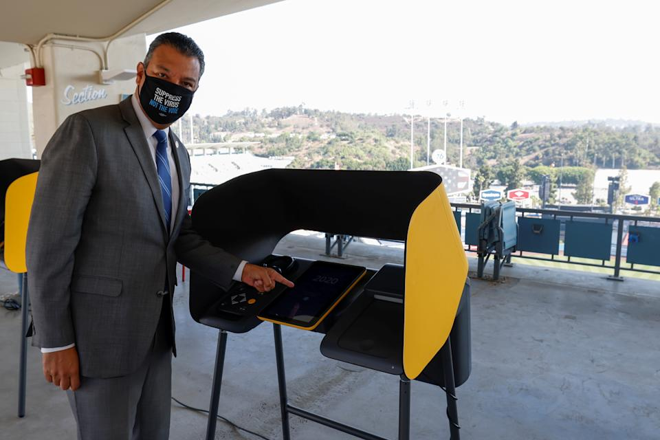 California Secretary of State Alex Padilla points to a voting booth at the Vote Center being set up for the U.S. general election at Dodger Stadium in Los Angeles, California, U.S., September 24, 2020.   REUTERS/Mike Blake