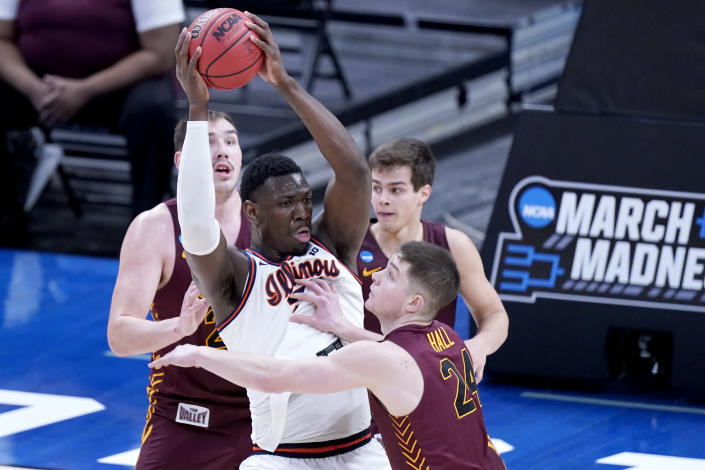 Illinois' Kofi Cockburn, center, is defended by Loyola of Chicago's Tate Hall (24) during the first half of a college basketball game in the second round of the NCAA tournament at Bankers Life Fieldhouse in Indianapolis Sunday, March 21, 2021. (AP Photo/Mark Humphrey)