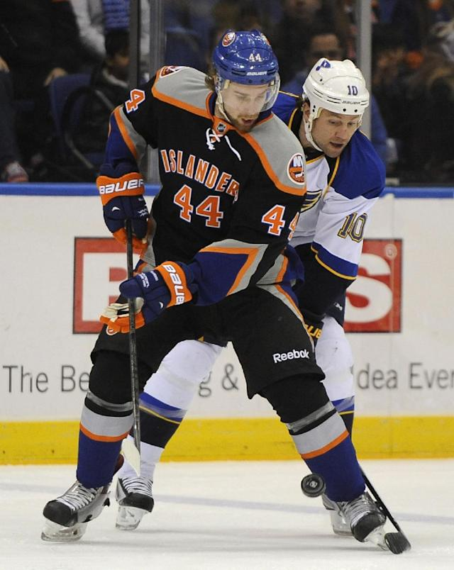New York Islanders' Calvin de Haan (44) and St. Louis Blues' Brendan Morrow battle for the puck in the first period of an NHL hockey game on Saturday, Jan. 25, 2014, in Uniondale, N.Y. (AP Photo/Kathy Kmonicek)