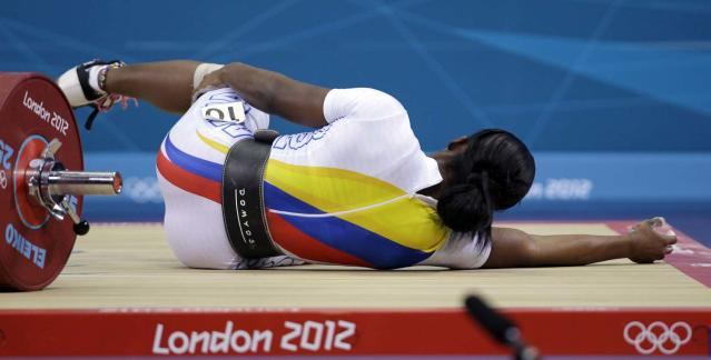 Lina Marcela Rivas of Colombia falls while competing during the women's 58-kg weightlifting competition at the 2012 Summer Olympics, Monday, July 30, 2012, in London. (AP Photo/Hassan Ammar)