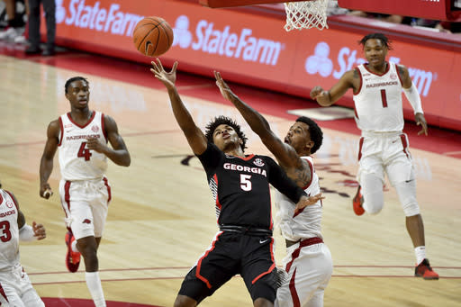 Georgia's Justin Kier (5) tries to drive past Arkansas defender Vance Jackson Jr. (2) during the first half of an NCAA college basketball game Saturday, Jan. 9, 2021, in Fayetteville, Ark. (AP Photo/Michael Woods)