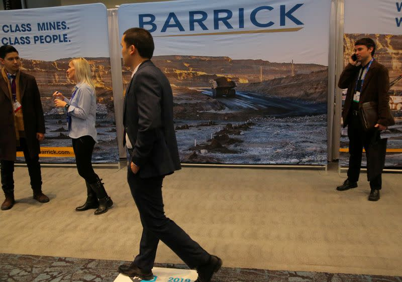 FILE PHOTO: A visitor passes a Barrick Gold mining company display during the PDAC convention in Toronto