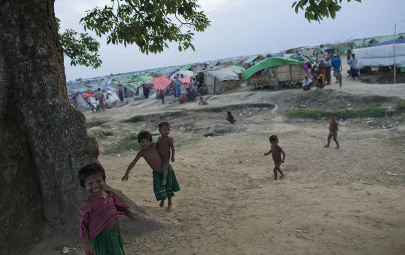 In this May 13, 2013 photo, internally displaced Rohingya children play in the foreground of makeshift tents at a camp for Rohingya people in Sittwe, northwestern Rakhine State, Myanmar. Authorities in Myanmar's western Rakhine state have imposed a two-child limit for Muslim Rohingya families, a policy that does not apply to Buddhists in the area and comes amid accusations of ethnic cleansing in the aftermath of sectarian violence. (AP Photo/Gemunu Amarasinghe)