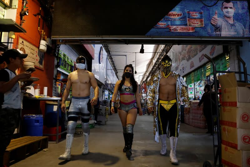 Lucha libre wrestlers arrive to encourage mask-less people to wear masks to aid the prevention against the continued coronavirus disease (COVID-19) at the Central Abastos market, in Mexico City