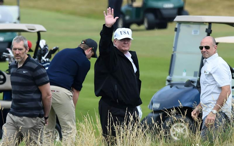 US President Donald Trump (C) gestures as he walks during a round of golf on the Ailsa course at Trump Turnberry - AFP
