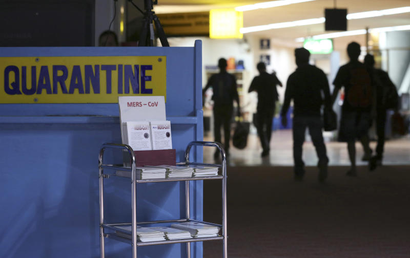 """FILE- In this Wednesday, April 16, 2014, file photo, passengers walk past the medical quarantine area showing information sheets for the Middle East respiratory syndrome coronavirus at the arrival section of Manila's International Airport in Paranaque, south of Manila. One expert says recent outbreaks of MERS in Saudi Arabia and the United Arab Emirates that led to more than 20 infections, many among health-care workers, """"have put us into uncharted territory."""" (AP Photo/Aaron Favila)"""