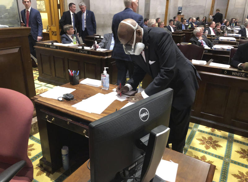 """FILE - In this March 19, 2020 file photo State Rep. G.A. Hardaway, D-Memphis, wears a mask during House floor proceedings in Nashville, Tenn., amid the coronavirus pandemic. Sharing information about people who have tested positive or been exposed to COVID-19 with first responders does not violate medical privacy laws, under guidance issued by the U.S. Department of Health and Human Services. That has not quelled skepticism about how the data is used. """"Tell us how it's working for you, then tell us how well it's been working; don't just tell us you need it for your job,"""" said Hardway, a Memphis Democrat who chairs the Tennessee Black Caucus. (AP Photo/Jonathan Mattise, file)"""