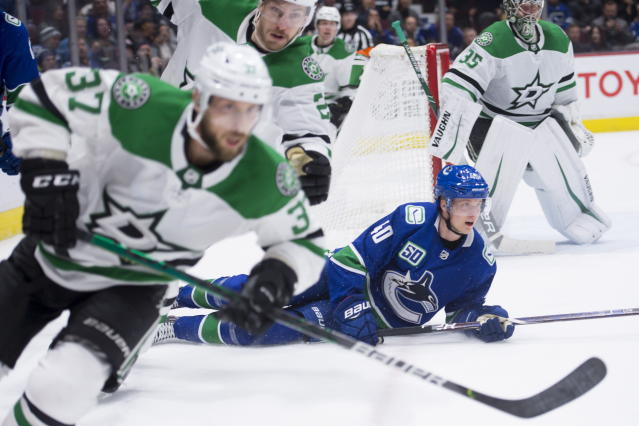 Vancouver Canucks center Elias Pettersson (40) lies on the ice after failing to get a shot past Dallas Stars goaltender Anton Khudobin (35) as Stars' Justin Dowling (37) skates by during the third period of an NHL hockey game Thursday, Nov. 14, 2019, in Vancouver, British Columbia. (Jonathan Hayward/the Canadian Press via AP)