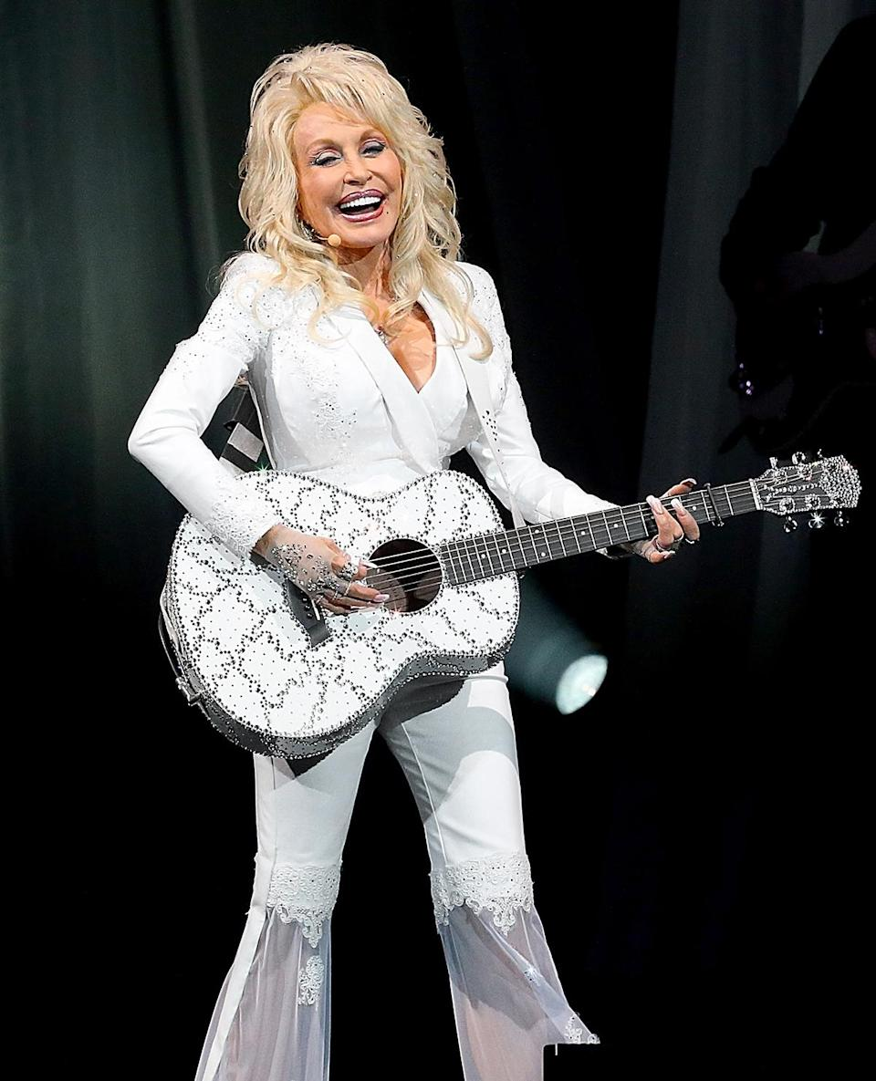 """<p>""""When I wear white, I feel like I'm singing to God,"""" said Parton, pictured on stage in 2016 in a white-hot suit.</p>"""