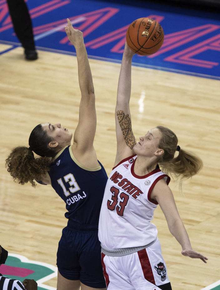 North Carolina State's Elissa Cunane (33) and Georgia Tech's Lorela Cubaj (13) vie for the opening tip off of an NCAA college basketball game in the semifinals of Atlantic Coast Conference tournament in Greensboro, N.C., Saturday, March 6, 2021. (AP Photo/Ben McKeown)
