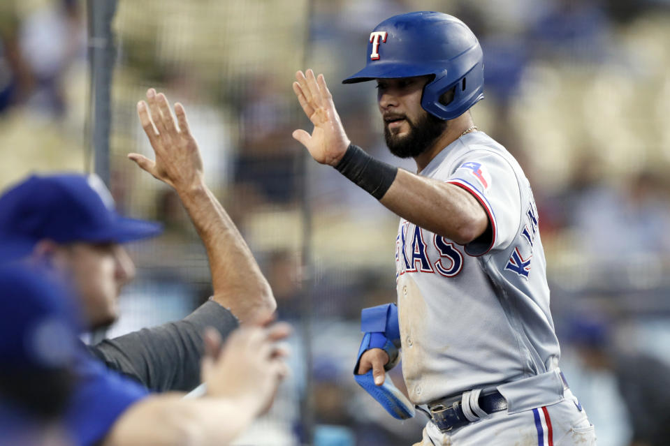 Texas Rangers' Isiah Kiner-Falefa gets a high-five after scoring on a double by Adolis Garcia against the Los Angeles Dodgers during the third inning of a baseball game in Los Angeles on Saturday, June 12, 2021. (AP Photo/Alex Gallardo)