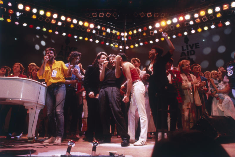 British pop acts gathered on stage for the finale of the Live Aid concert at Wembley Stadium in London, 13th July 1985. The group includes George Michael, left in yellow shirt, centre stage Bono, Paul McCartney and Freddie Mercury share a microphone, David Bowie is behind them and Howard Jones is on the right. Event organiser Bob Geldof stands next to George Michael. (Photo by Dave Hogan/Getty Images)