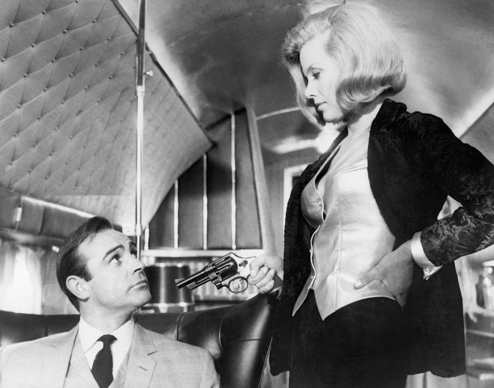"""(Original Caption) 1964: A scene from United Artist's production of """"Goldfinger,"""" in which James Bond prevents gold smugglers from robbing the United States' gold supply at Fort Knox. In this scene, Honor Blackman as """"Pussy Galore"""" points a gun at Sean Connery as """"James Bond."""" (Photo by �� John Springer Collection/CORBIS/Corbis via Getty Images)"""