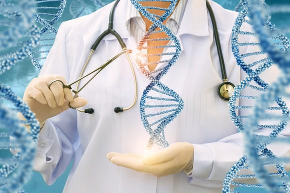 A person in a white lab coat with a stethoscope around their neck uses scissors to snip away at an image of a double helix being held in their hand.