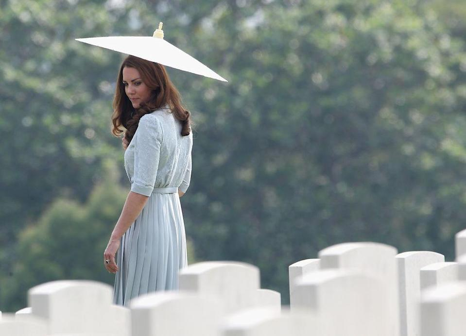 <p>Kate Middleton walks through Kranji Commonwealth War Cemetery in Singapore, shielded by a parasol.<br></p>