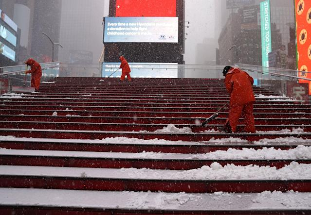 <p>Workers clean steps at Times Square in New York on March 21, 2018, as the fourth nor'easter in a month hits the tri-state area on the first full day of spring. (Photo: Timothy A. Clary/AFP/Getty Images) </p>