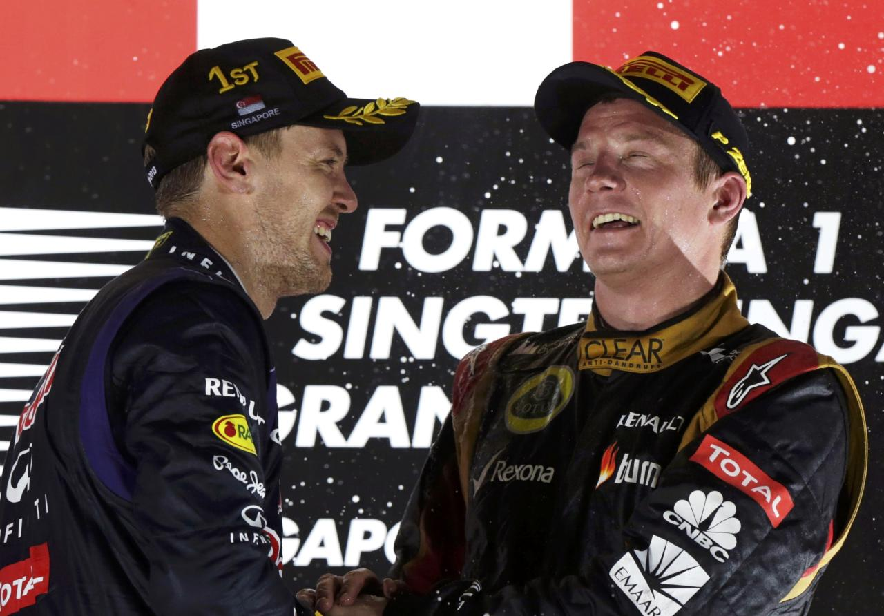 Red Bull Formula One driver Sebastian Vettel of Germany (L) celebrates on the podium with Lotus F1 Formula One driver Kimi Raikkonen of Finland after the Singapore F1 Grand Prix at the Marina Bay street circuit in Singapore September 22, 2013. REUTERS/Pablo Sanchez (SINGAPORE - Tags: SPORT MOTORSPORT F1)