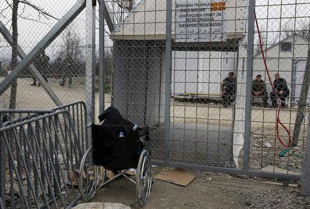 Stranded wheelchair-bound Zhino Hasan, 17, is seen in front of the closed Idomeni border gate, hoping that Macedonia would relent and allow her and her family to resume their northward trek through the Balkans to Germany February 26, 2016. REUTERS/Yannis Behrakis