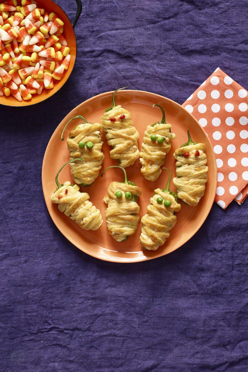 "<p>Wrap jalapeno poppers with puff pastry, then add roasted red pepper or peas for mummy eyes.</p><p><strong><a href=""https://www.womansday.com/food-recipes/food-drinks/recipes/a56191/hot-pepper-mummies-recipe/"" rel=""nofollow noopener"" target=""_blank"" data-ylk=""slk:Get the recipe"" class=""link rapid-noclick-resp"">Get the recipe</a>.</strong></p>"