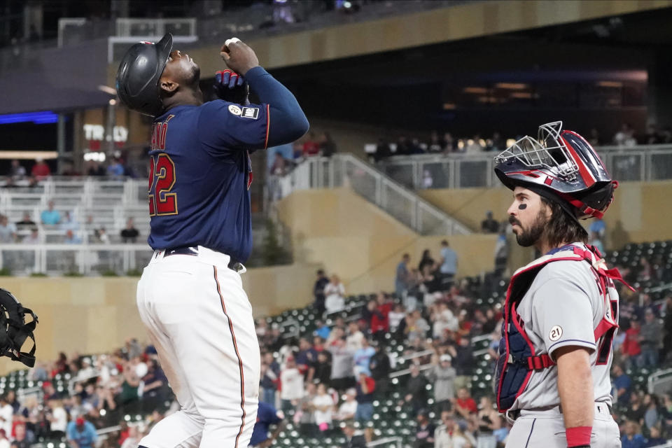 Minnesota Twins' Miguel Sano, left, looks skyward as he scores past Cleveland Indians catcher Austin Hedges on a three-run home run off Indians pitcher Cal Quantrill (47) in the seventh inning of a baseball game, Wednesday, Sept. 15, 2021, in Minneapolis. The Indians won 12-3. (AP Photo/Jim Mone)