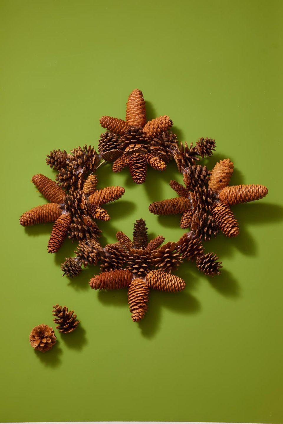 """<p>Bring a little bit of the outdoors to your front door. Start by laying out the pinecones in the shape that you want. Then, hot glue all of the pinecones to a <a href=""""https://www.amazon.com/Darice-170150-Floral-Metal-Wreath/dp/B0054G5JQK?tag=syn-yahoo-20&ascsubtag=%5Bartid%7C10055.g.2996%5Bsrc%7Cyahoo-us"""" rel=""""nofollow noopener"""" target=""""_blank"""" data-ylk=""""slk:wire wreath form"""" class=""""link rapid-noclick-resp"""">wire wreath form</a>, starting with the main circle. Continue to glue the pinecones into five-pointed-star shapes. You may need to use a little wire and extra hot glue to secure a few pinecone tips that are hard to line up. </p>"""