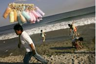<p>A man walks the Coney Island beach selling cotton candy to kickstart summer on Memorial Day weekend.</p>