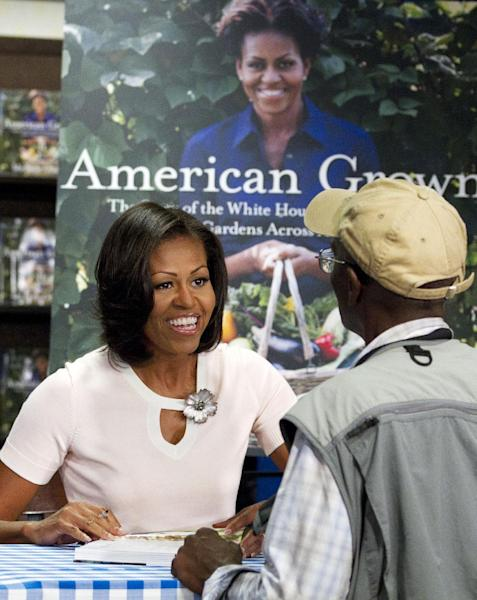 "First lady Michelle Obama signs copies of her book ""American Grown: The Story of the White House Kitchen Garden and Garden Across America,"" in Washington, Tuesday, June 12, 2012. (AP Photo/Jacquelyn Martin)"