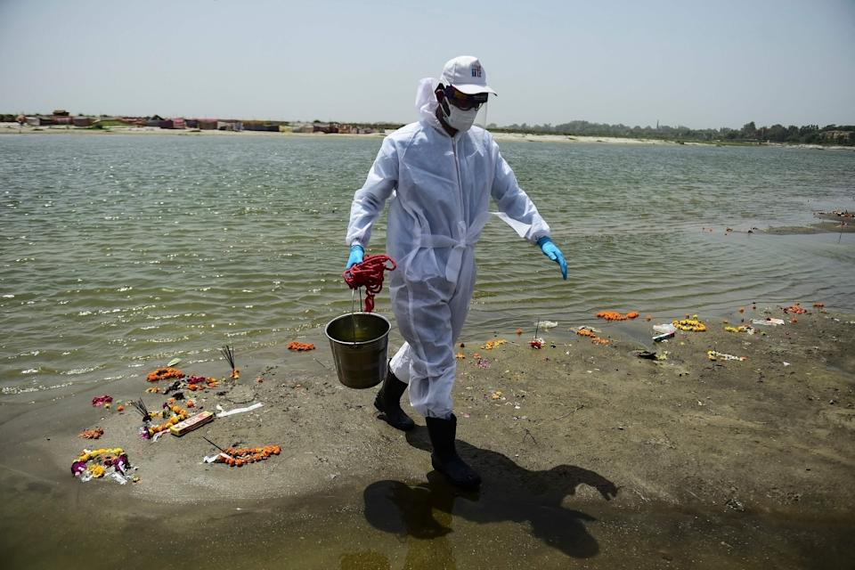 A member of Indian Institute of Toxicology Research collects sample from river Ganges on 24 May, 2021 (AFP via Getty Images)