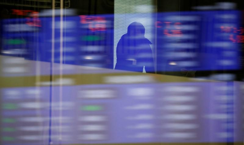 A visitor is seen as market prices are reflected in a glass window at the Tokyo Stock Exchange (TSE) in Tokyo, Japan, February 6, 2018. REUTERS/Toru Hanai