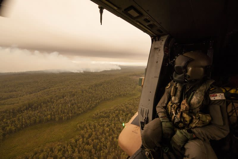 A Royal Australian Navy MRH-90 helicopter crew member, observes the fires on approach to Cann River in Gippsland