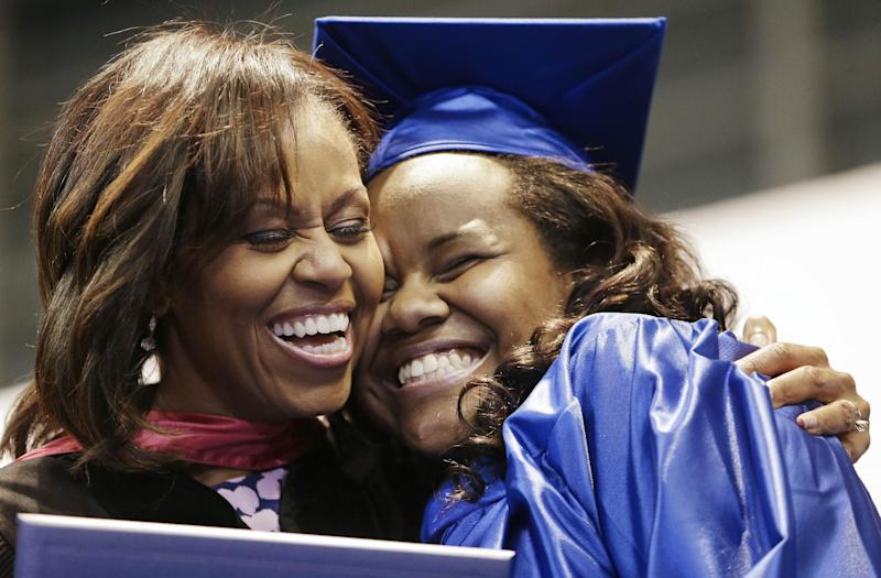 First lady Michelle Obama hugs Jenika Headley-Greene as Obama hands out diplomas during the graduation ceremony for Martin Luther King Jr. Academic Magnet High School, Saturday, May 18, 2013, in Nashville, Tenn. (AP Photo/Mark Humphrey)