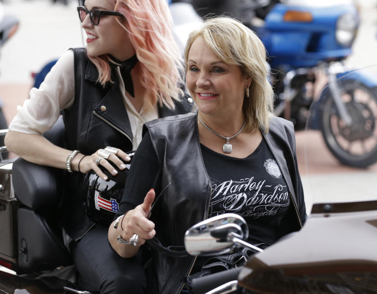 Oklahoma Governor Mary Fallin gives a thumbs up after riding a Harley Davidson motorcycle to the motorcycle museum Friday, August, 2, 2013 in Milwaukee. The National Governors Association is meeting in Milwaukee. (AP Photo/Jeffrey Phelps)