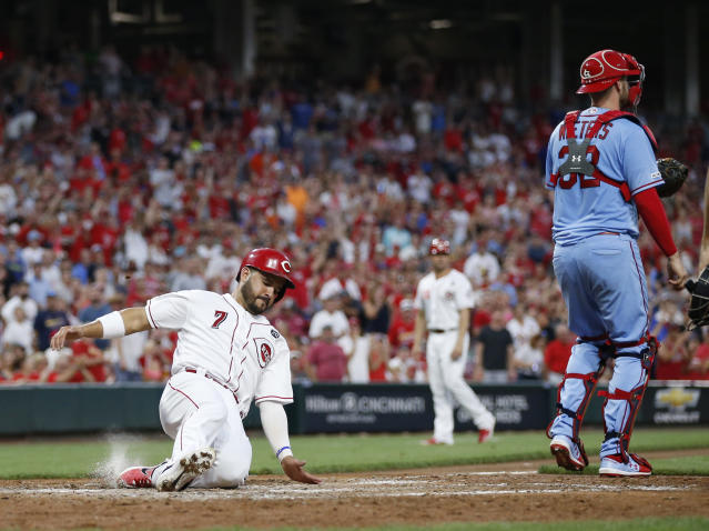Cincinnati Reds' Eugenio Suarez (7) scores on a double off the bat of Yasiel Puig as St. Louis Cardinals catcher Matt Wieters (32) waits a throw during the seventh inning of a baseball game, Saturday, July 20, 2019, in Cincinnati. (AP Photo/Gary Landers)