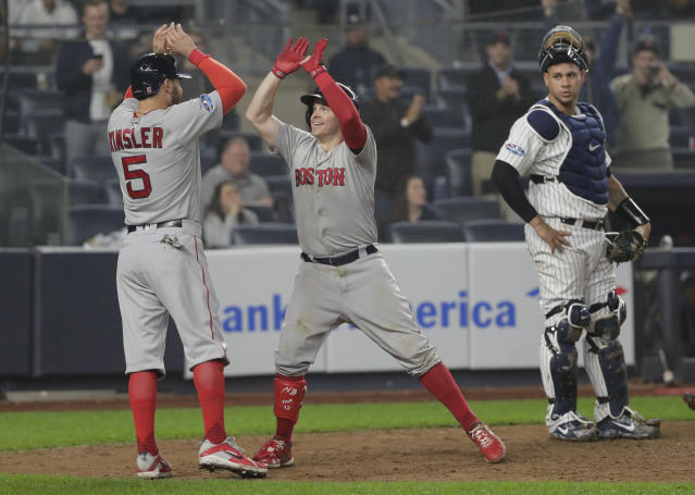 Boston Red Sox's Brock Holt, center, celebrates with Ian Kinsler (5) after hitting a two-run home run against the New York Yankees during the ninth inning of Game 3 of baseball's American League Division Series, Monday, Oct. 8, 2018, in New York. Holt hit for the cycle in the Red Sox's 16-1 win. (AP Photo/Frank Franklin II)