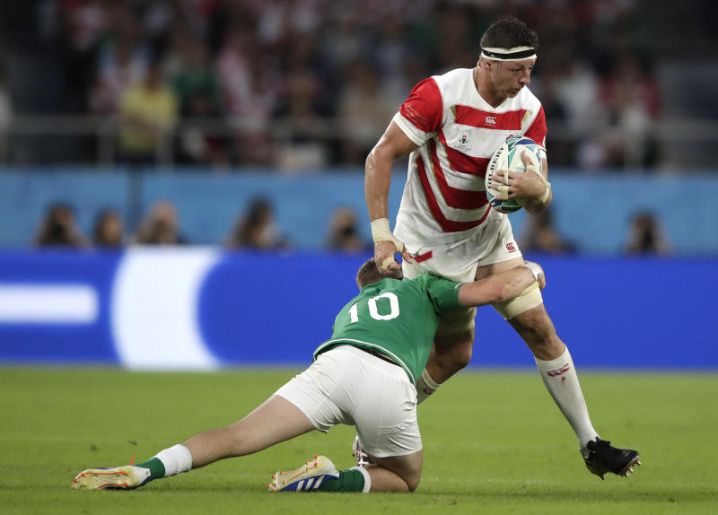 Japan's Luke Thompson is tackled by Ireland's Jack Carty during the Rugby World Cup Pool A game at Shizuoka Stadium Ecopa between Japan and Ireland in Shizuoka, Japan, Saturday, Sept. 28, 2019. (AP Photo/Jae Hong)