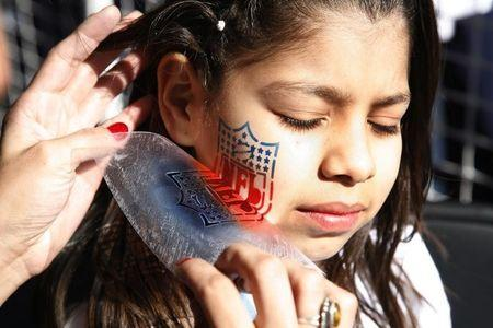 A child has the National Football League logo airbrushed on her cheek at the NFL Experience
