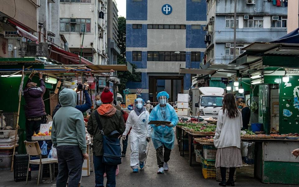 Health workers patrol on a street where COVID-19 cases have been confirmed in the Jordan district in Hong Kong - Getty