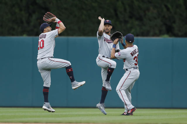 Minnesota Twins left fielder Eddie Rosario (20), center fielder Byron Buxton, right fielder LaMonte Wade Jr., celebrate after the team's 8-3 over the Detroit Tigers in a baseball game, Sunday, Sept. 1, 2019, in Detroit. (AP Photo/Carlos Osorio)