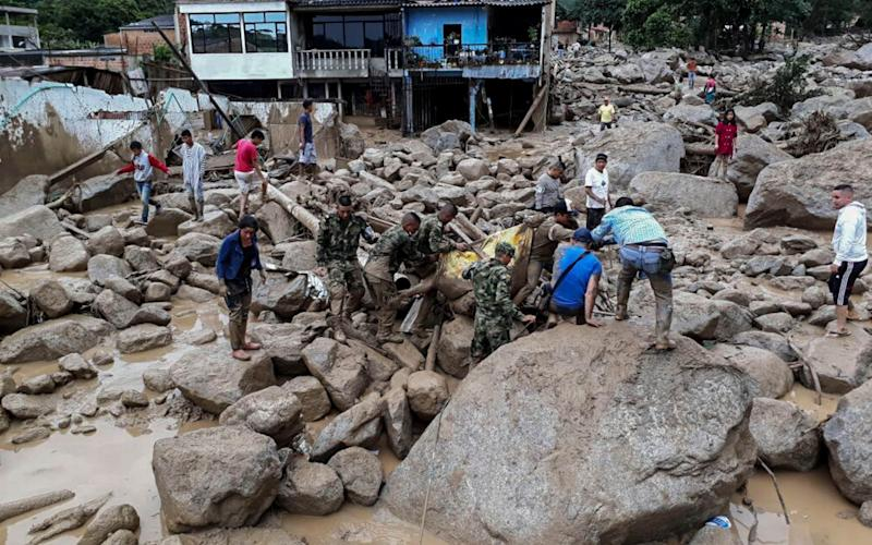 Soldiers take away a body following mudslides caused by heavy rains, in Mocoa - Credit: AFP