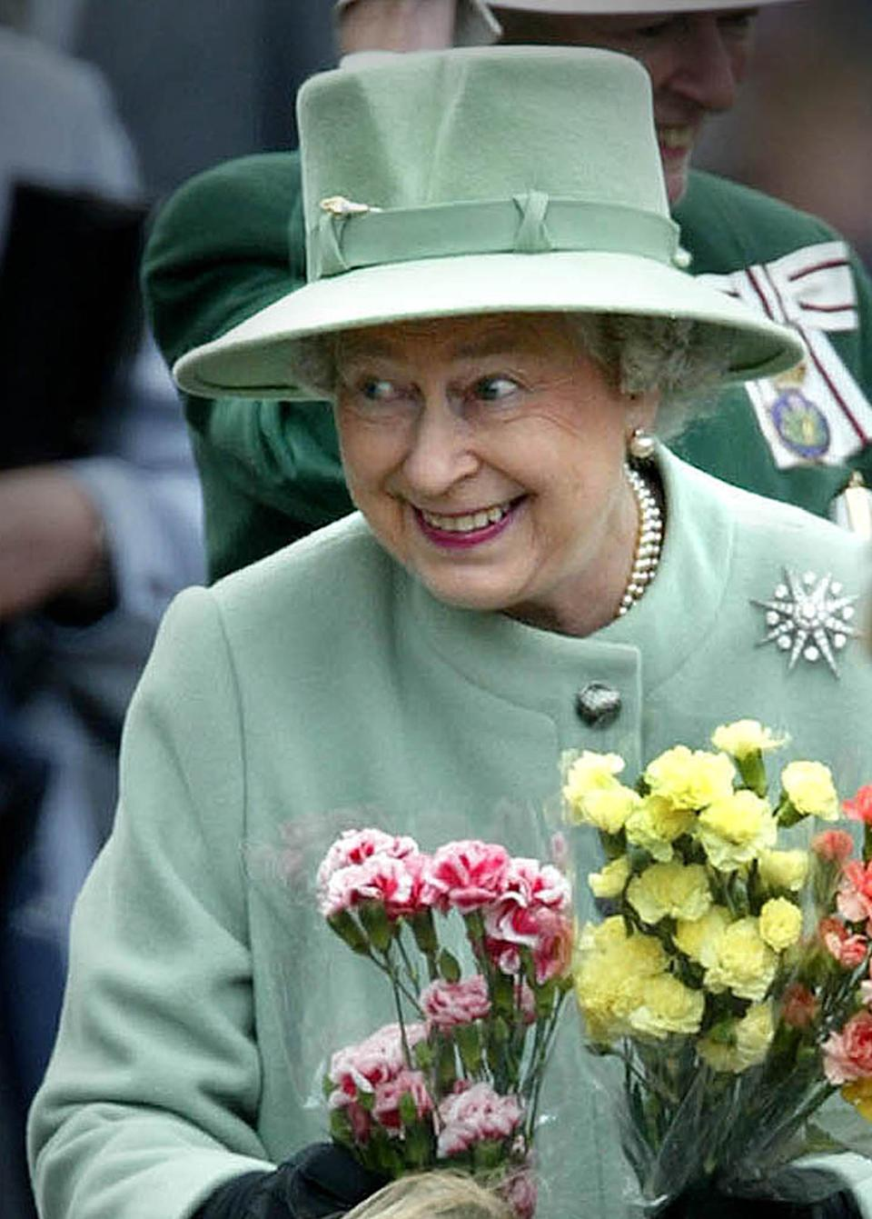 Britain's Queen Elizabeth shows her delight as she is presented with flowers from children during her walkabout on Melrose Market square in the Scottish Borders May 29, 2002. REUTERS/Jeff J Mitchell  JJM/PS