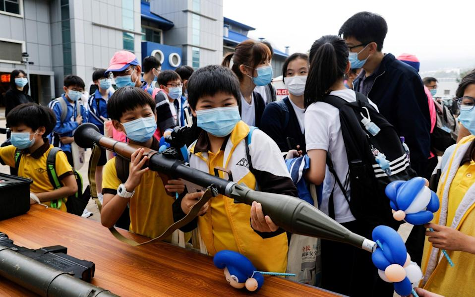 Children play with a mock rocket launcher at Hong Kong Police College - Reuters