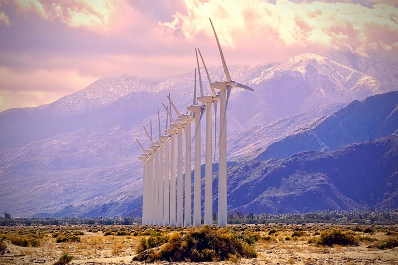 A line of wind turbines with mountains in the background.