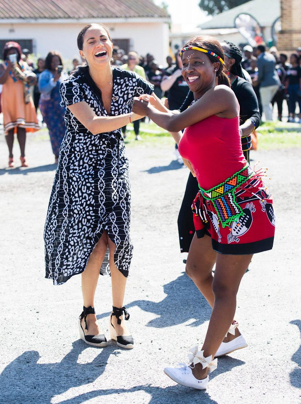 """<p>Anything a man can do, she can do backward — and in wedges! Four months after welcoming son Archie, Meghan Markle dazzled during a visit to Nyanga Township with Prince Harry in Cape Town, South Africa. The couple had """"great"""" skills, local resident Nosisana Nama told PEOPLE in 2019. """"They've got their African moves.""""</p>"""