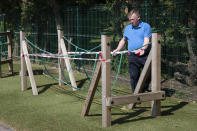 Head teacher Graham Hamilton tapes off playground equipment as measures are taken to prevent the transmission of coronavirus before the possible reopening of Lostock Hall Primary school in Poynton near Manchester, England, Wednesday May 20, 2020. (AP Photo/Jon Super)
