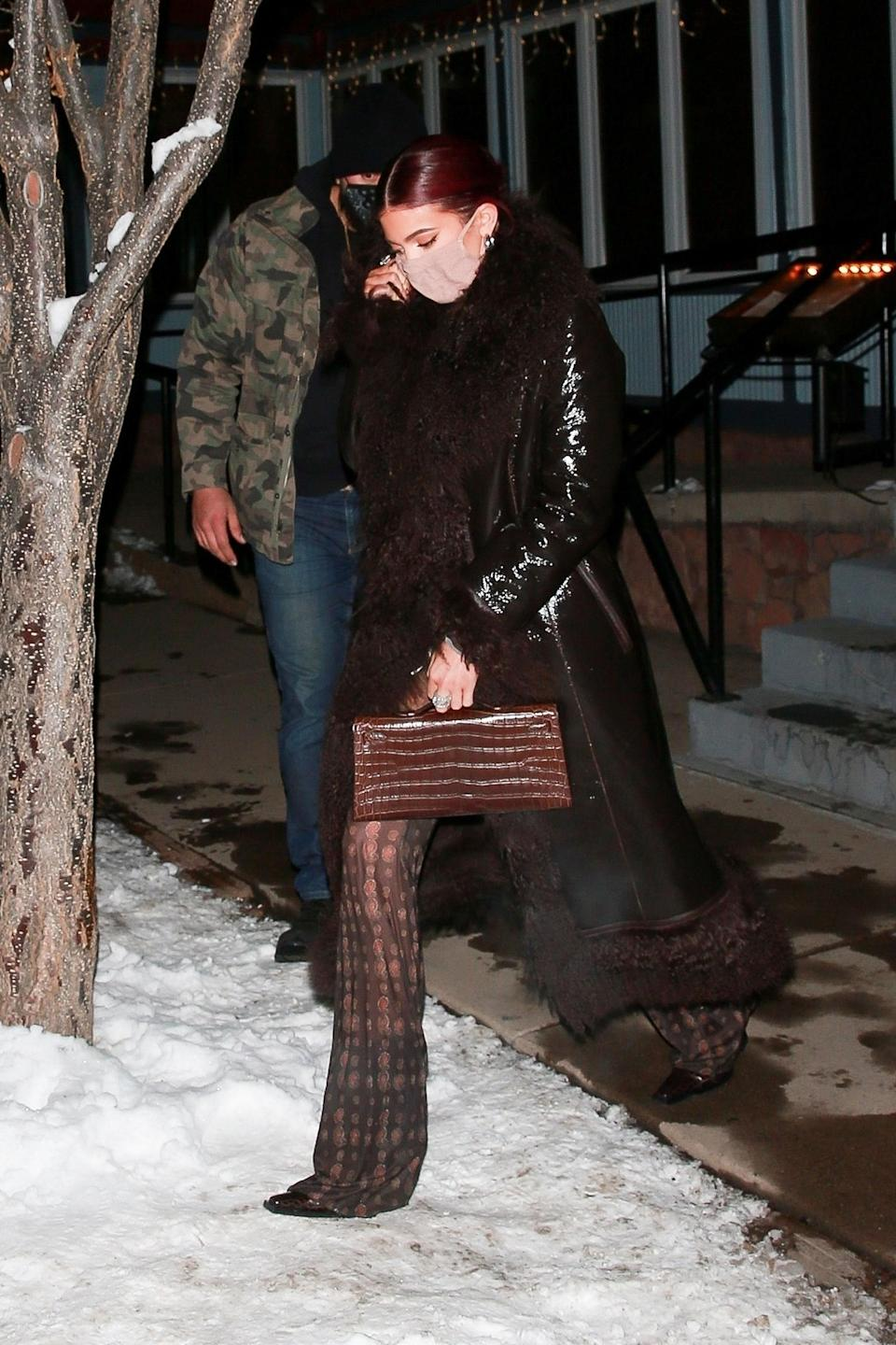 <p>WHO: Kylie Jenner</p> <p>WHAT: Saks Potts coat, Charlotte Knowles top and pants, Hermes clutch, Skims face mask</p> <p>WHERE: Aspen, Colorado</p> <p>WHEN: December 30</p>