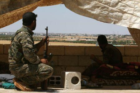 Fighters of the Syria Democratic Forces (SDF) sit in a look out position in the western rural area of Manbij