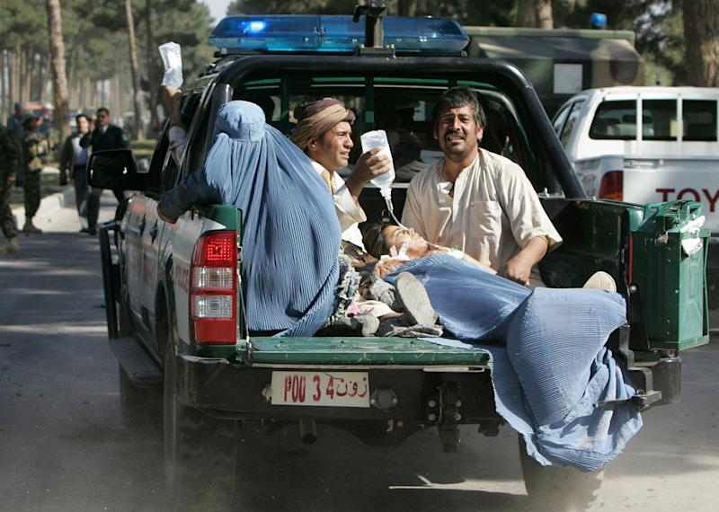 Afghan victims of a suicide attack are transported in the back of a police truck in Guzara, Herat province, west  of Kabul, Afghanistan, Tuesday, April 10, 2012. A suicide blast blew up a four-wheel-drive vehicle during rush hour Tuesday outside a government office in Herat province in western Afghanistan, killing and wounding scores of people, authorities said. (AP Photo/Hoshang Hashimi)