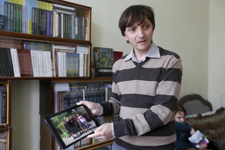 """Volodymyr Yavorskyy shows a family photo during his interview with The Associated Press in Kyiv, Ukraine, Friday, May 28, 2021. His wife, Tatsiana Hatsura-Yavorska, leads a rights group in Belarus that helps those released from prison adapt to life, and was herself arrested on charges of """"organizing actions that violate public order,"""" and cannot leave the country. He says authorities in Belarus ordered him out of the country and he cannot return for 10 years. (AP Photo/Efrem Lukatsky)"""