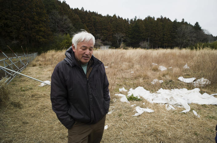 Naoto Matsumura speaks during an interview with The Associated Press at his farm land in Tomioka town, Fukushima prefecture, northeastern Japan, Friday, Feb. 26, 2021. About 10 kilometers (6 miles) south of the wrecked Fukushima Dai-ichi nuclear power plant, rice farmer Matsumura defied a government evacuation order and stayed on his farm to protect his land the cattle abandoned by neighbors a decade ago. (AP Photo/Hiro Komae)